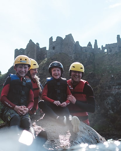 Image of smiling happy family in front of Dunluce Castle, near Portrush on the North Coast of Northern Ireland